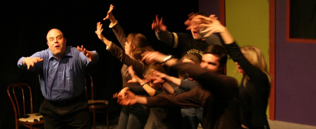 Group in improv with hands up