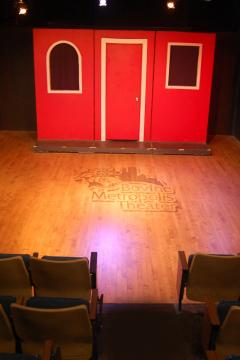 Empty stage with red building